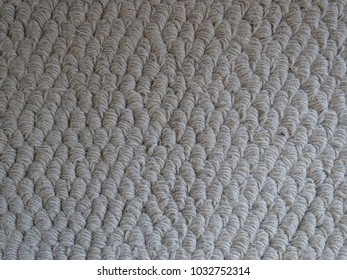 A close up background in beige  of a textured, high pile carpet