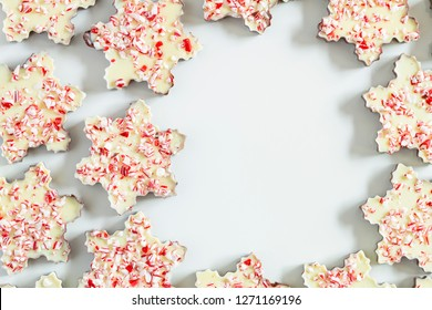 Close up of background of chocolate peppermint bark snowflakes arranged in a circle with blank space for text