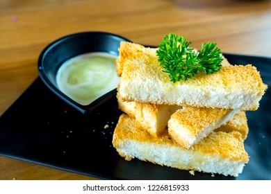 Close up background of Grilled Crispy bread with sweet pandan custard. Sweet snacks homemade style grilled crispy bread served with green Pandan custard.
