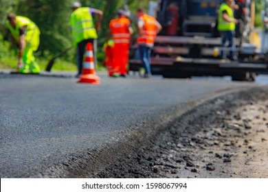 Close up background of a new road and paving machine on it that was recently paved with builders in uniform on the back fon