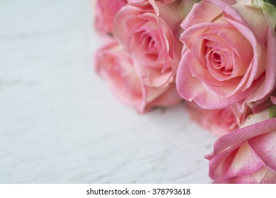 Close up background with pink roses over white wooden table. Top view with copy space