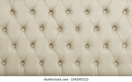 Close up background texture of beige white capitone genuine leather, retro Chesterfield style soft tufted furniture upholstery with deep diamond pattern and buttons