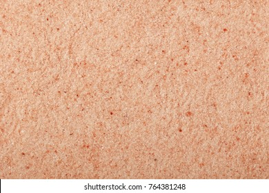 Close up background texture of small fine ground crystals pink Himalayan salt, elevated top view, directly above