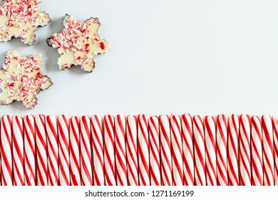 Close up of background of three chocolate peppermint bark snowflakes with row of red and white striped peppermint candies and blank space for text