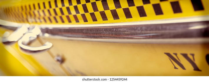 Close up background vintage panoramic web banner photograph of the side of New York City Yellow Taxi Cab