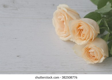 Close up background with yellow roses over white wooden table. Top view with copy space