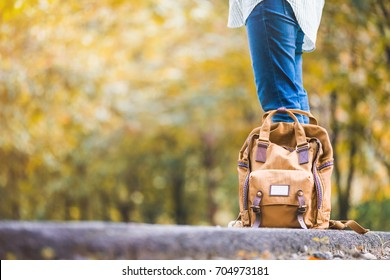 Close up backpack of woman backpacker standing on countryside road with tree in autumn fall seasonal,Alone travel or single traveler concept
