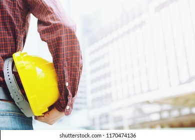 Close up backside view of engineering male construction worker stand holding safety yellow helmet  for the safety of the work operation. outdoor of building background.