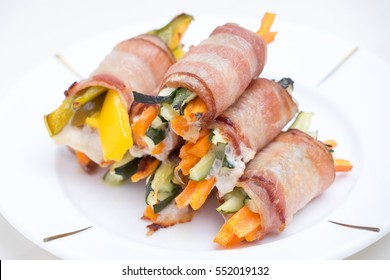 Close up of bacon rolls stuffed with carrots, pepper & cucumber on white plate.