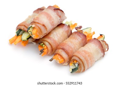 Close up of bacon rolls stuffed with carrots, pepper & cucumber on white background.