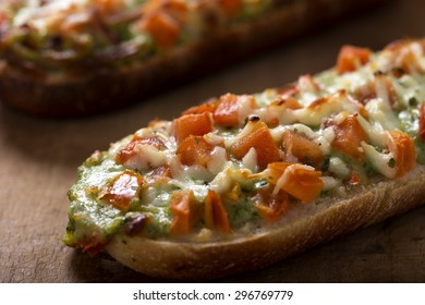 Close up of Baguettes with pesto on rustic wooden background