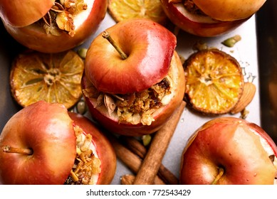 Close up of baked red apples with granola, cinnamon, nuts and honey. Healthy fruit dessert
