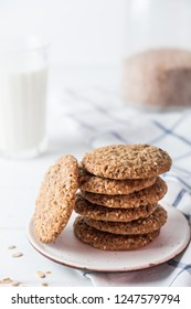 Close up of baked wholegrain cookies on white wooden table with milk on background