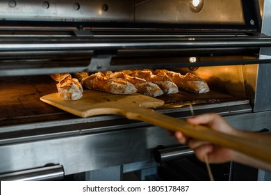 Close up of baker is taking off from oven the french baguette bread with wood peel at baking manufacture factory. French baguette bread bakery factory concept.