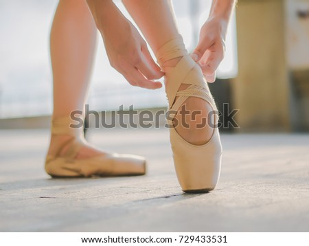 0ee1067b6 Close up of a ballet dancer s feet as she practices pointe exercises on the  stone embankment. Woman s feet in pointe shoes. Ballerina shows classic  ballet ...