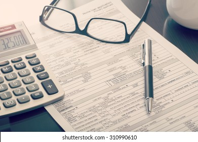 Close up of a bank home loan  application form on desk with calculator and eye glasses