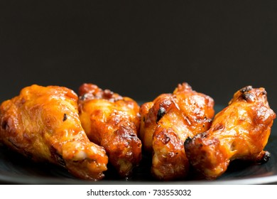 Close up of barbecue chicken wings in black background empty space for text