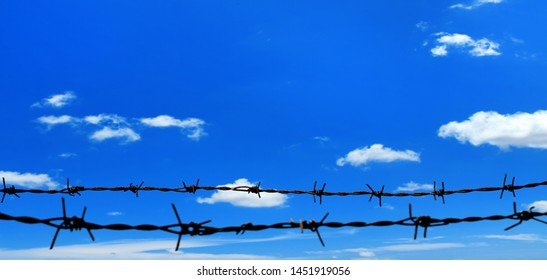 close up barbed wire fence over sunny blue sky