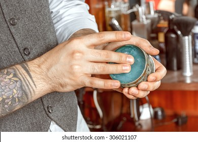close up of barbers hand and a gel jar