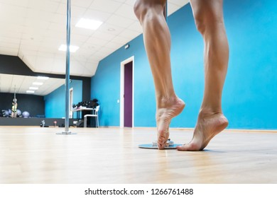 Close up of bare brawny legs of a poledancer posing before poledance at dance hall background. Girl's strong legs standing on tiptoe near the steel pole at dancefloor. Strength of pole dancing