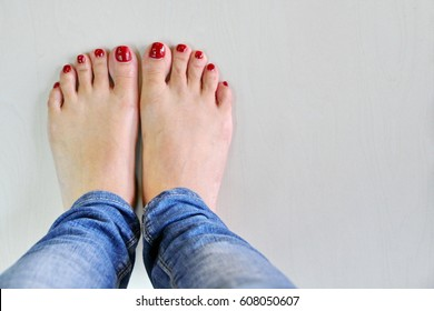 Close up bare feet of female and wears blue jeans. Female feet stand on the ground floor.