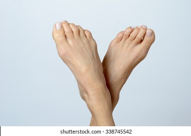 Close up Bare Feet of a Woman Pointing Up Against Gray Background with Copy Space.