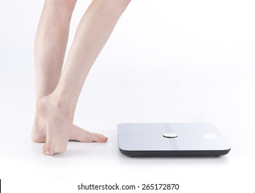 Close up Bare Female Feet and Legs Standing on the Floor Near a Smart Body Analyzer Technology for Measuring Weights, Isolated on White Background.
