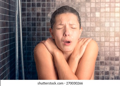 Close up Bare Young Woman Reacting While Taking Cold Shower with Arms Crossing Over her Chest and Eyes Closed.