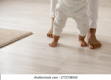 Close up barefoot African American woman with toddler child standing on warm wooden floor with underfloor heating, caring loving young mum teaching adorable little daughter to walk at home