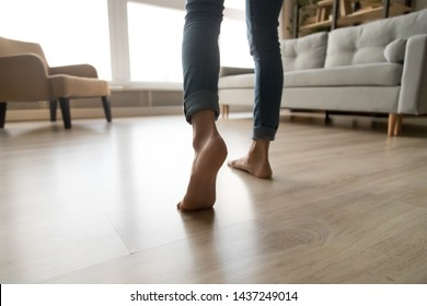 Close up of barefoot young woman in jeans feel comfortable walking on warm heated wooden floor at home, female step in her bare feet relaxing enjoy free sunny day in own modern apartment