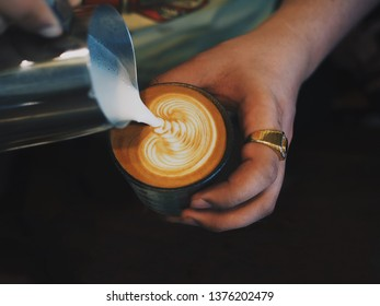 Close up barista hands pouring milk in coffee cup for making latte art.