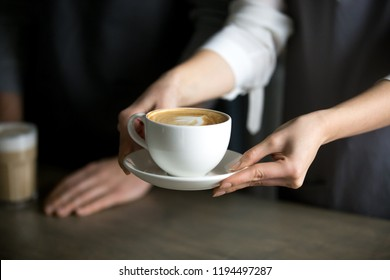 Close up of barista holding aromatic cappuccino, serving it to coffeeshop visitor, waitress giving cup of fresh brewed coffee with milk foam to café guest, bringing latte drink to coffeehouse table