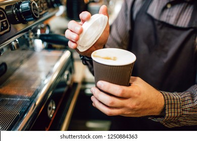 Close up of barista holding cup of coffee and lid. He is going to put lid on cup. Guy stand at coffee machine.