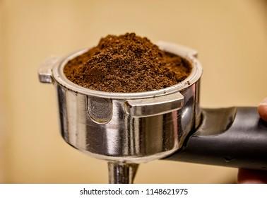 Close up of barista holding portafilter for espresso coffee machine. Espresso preparation.