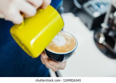 Close up of barista pouring steamed milk into coffee cup making latte art.