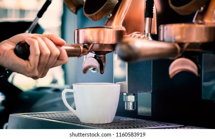 Close up of barista preparing fresh espresso on professional brewing machinery