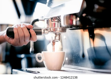 Close up of barista preparing fresh espresso on porfessional brewing machinery