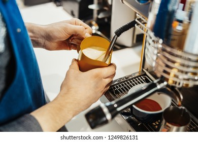 Close up of barista steaming milk in the pitcher with coffee machine.