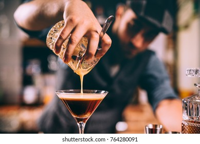 close up of barman hand pouring alcoholic cocktail in martini glass