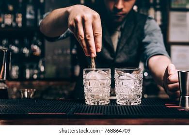 Close up of barman hands pouring sugar in old fashioned cocktail. fresh beverages at bar