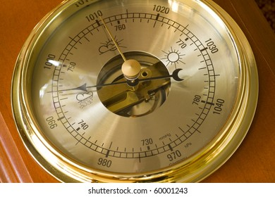 A close up of a barometer pointing towards the hurricane setting.