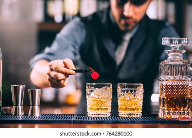 Close up of bartender hands preparing old fashioned whiskey cocktail on bar counter