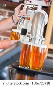 Close Up Of Bartender Pouring Pint Of Beer Behind Counter - Shutterstock ID 1586725918