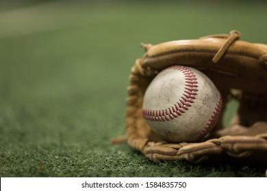 Close up of baseball in mitt on turf