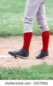 close up of baseball players legs with bright red stockings standing on first base