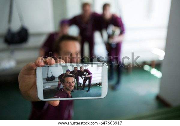 Close up of baseball team clicking selfie while standing at locker room after match