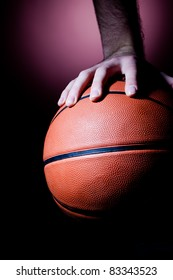 Close up of basketball player's hand on the ball
