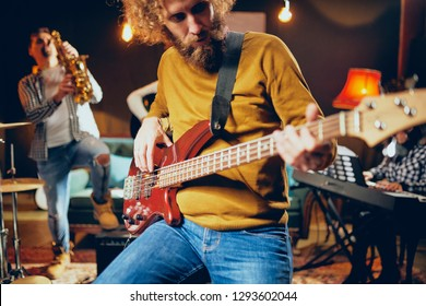 Close up of bass guitarist playing guitar while sitting on the chair. In background rest of the band. Home studio interior.