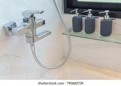 close up of bathtub faucet with three bottle of hygiene liquid such as shampoo,bath gel, conditioner.
