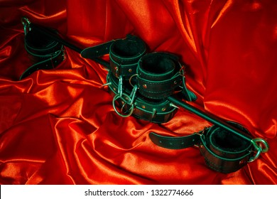 Close up bdsm outfit. Bondage, kinky adult sex games, kink and BDSM lifestyle concept with a pair of leather handcuffs, flogger, a leash attached on red silk with copy space.